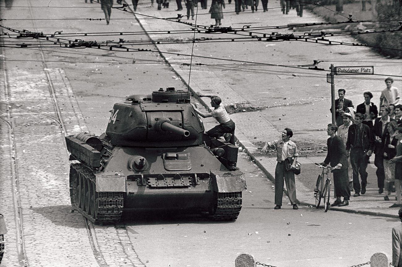 صورة لأحد أهالي برلين الشرقية أثناء محاولته تسلق إحدى الدبابات السوفيتية