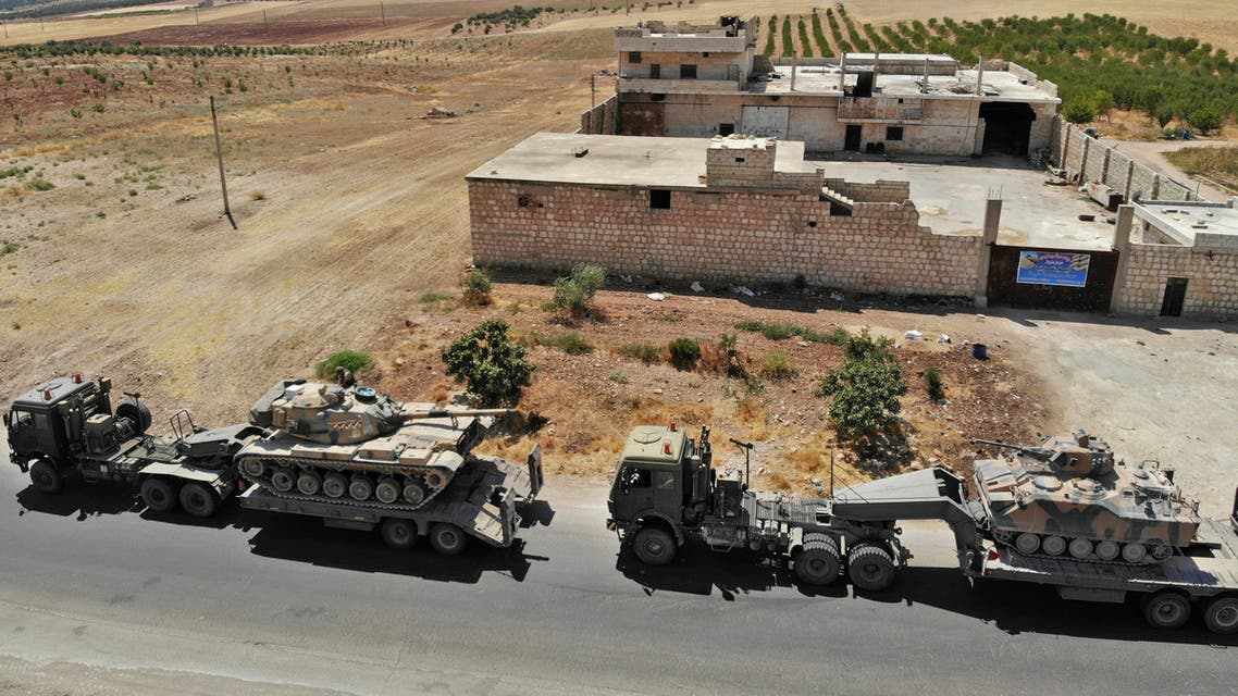 A convoy of Turkish military vehicles is pictured near the town of Maar Hitat as smoke billows in the background, during reported air strikes by pro-regime forces in northern Syria's Idlib province on August 19, 2019. A Turkish military convoy crossed into northwest Syria today, heading towards a key town where regime forces are waging fierce battles with jihadists and rebels.