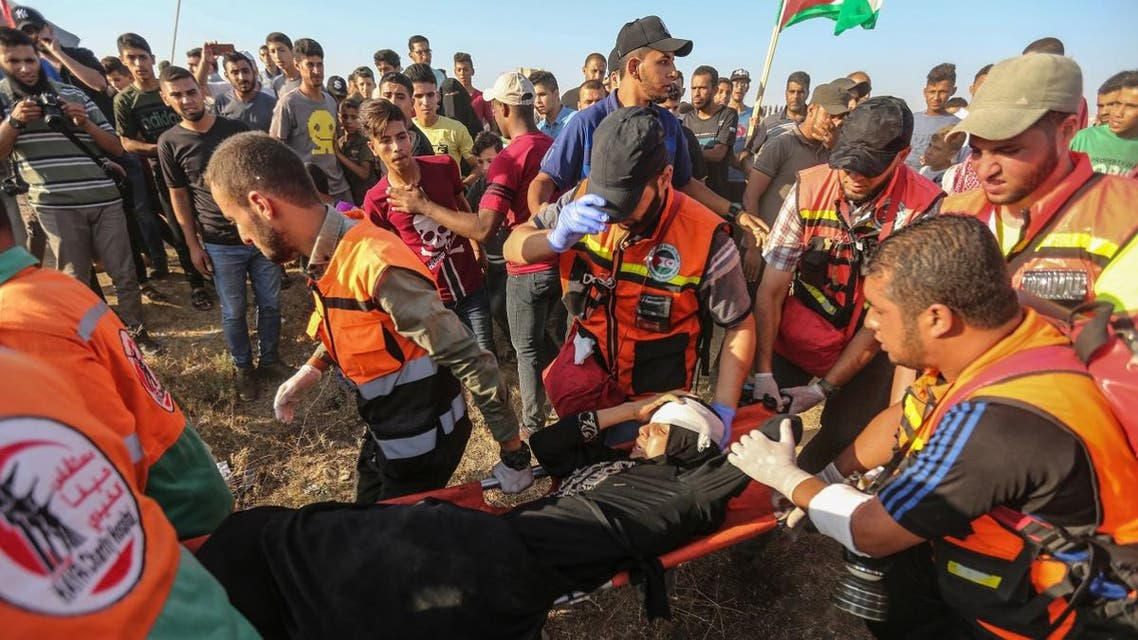 Palestinian paramedics carry a wounded protester during clashes with Israeli forces near the fence along the border with Israel in the eastern Gaza Strip on August 16, 2019. (AFP)
