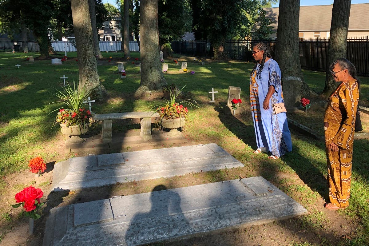 Earline Jackson (right), and Phyllis Bradshaw stand at a relative's grave in the Tucker Family Cemetery in Hampton, Virginia, on August 23, 2019.  (AP)