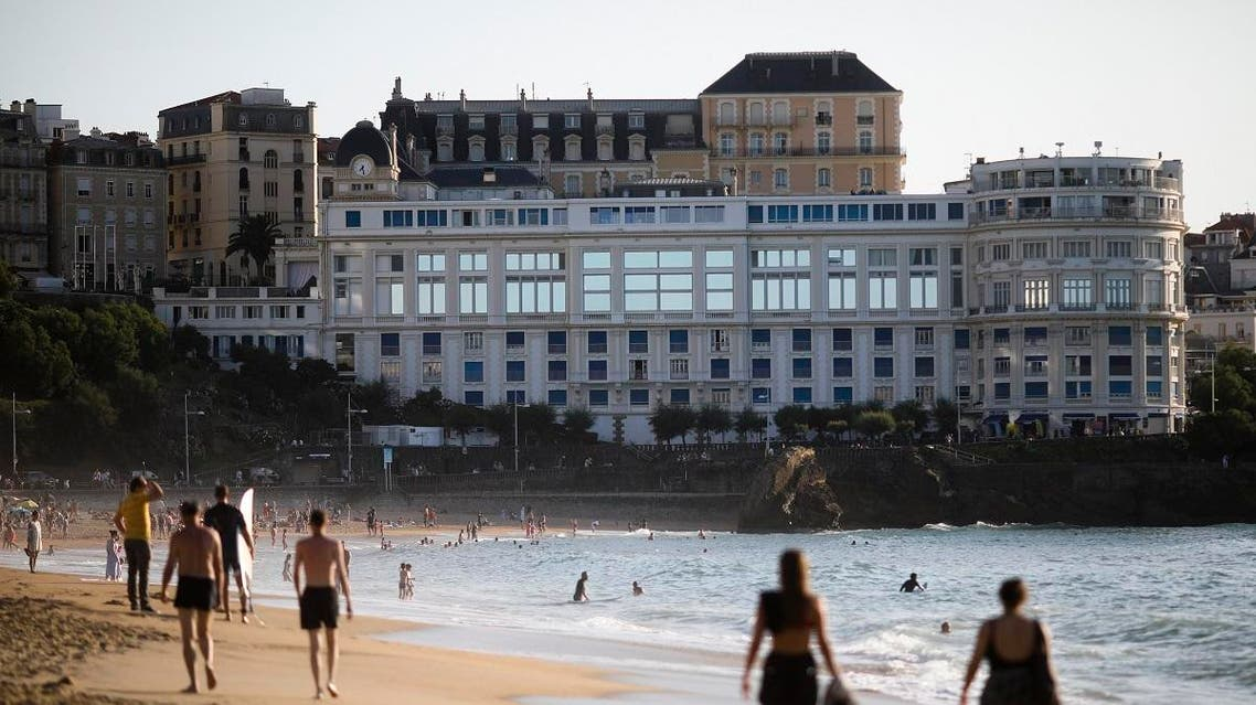 People walk at the beach in front of the G7 summit venue Le Bellevue, on August 21, 2019, in Biarritz, southwestern France. (AP)