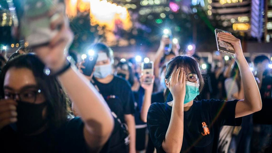 Secondary school students cover their right eye as they hold up their phone torches while attending a rally at Edinburgh Place in Hong Kong on August 22, 2019. (AFP)