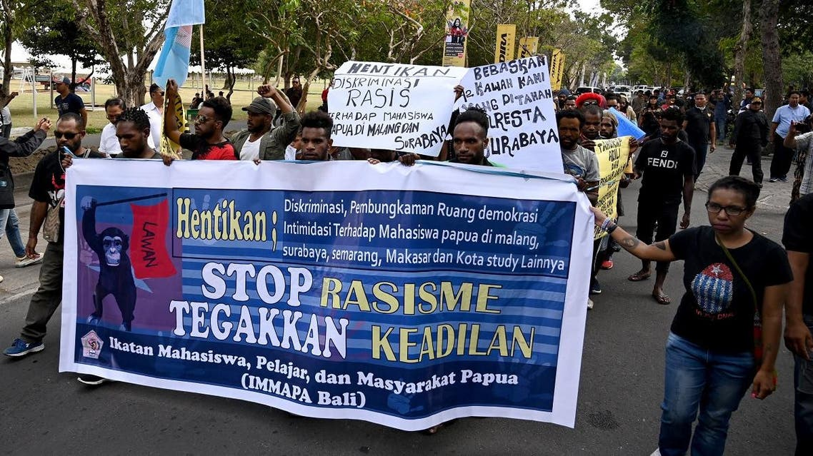 People hold banners and placards against the recent surge in violent protests in Indonesia's eastern Papua province. (AFP)