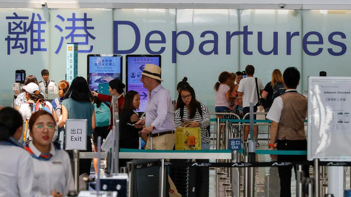 Airport staff help travellers near the departure gate at the airport in Hong Kong, Wednesday, Aug. 14, 2019. (AP)
