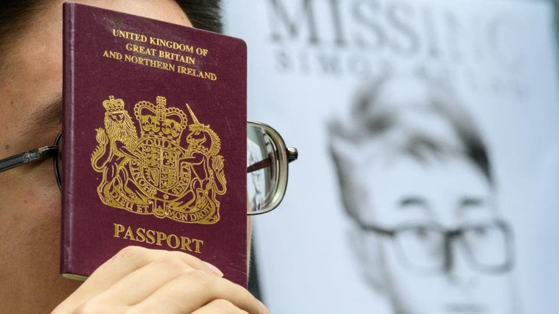 An activist holds a British passport during a gathering outside the British Consulate-General building in Hong Kong on August 21. (AFP)