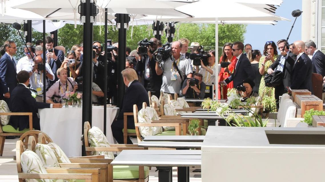 The press corps gather as US President Trump (R) sits to lunch with French President Macron (L), at the Hotel du Palais in Biarritz, on the first day of the annual G7 Summit on August 24, 2019. (AFP)