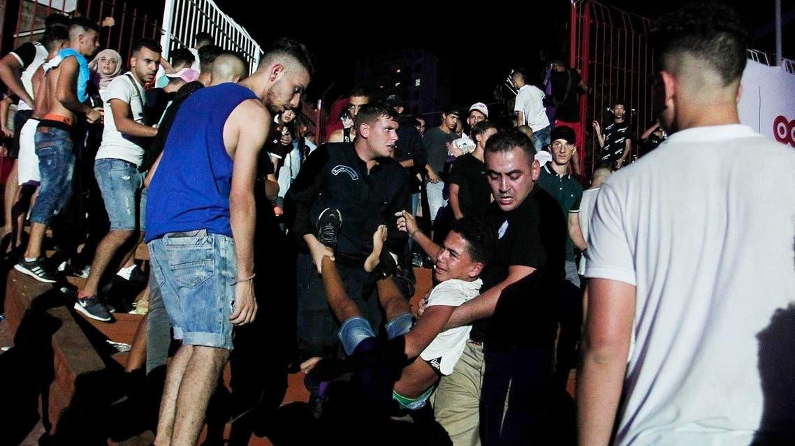 A man is evacuated during Algerian rap artist Abderraouf Derradji's concert, known as Soolking, at a stadium in Algiers, Thursday, Aug. 22, 2019. (AP)
