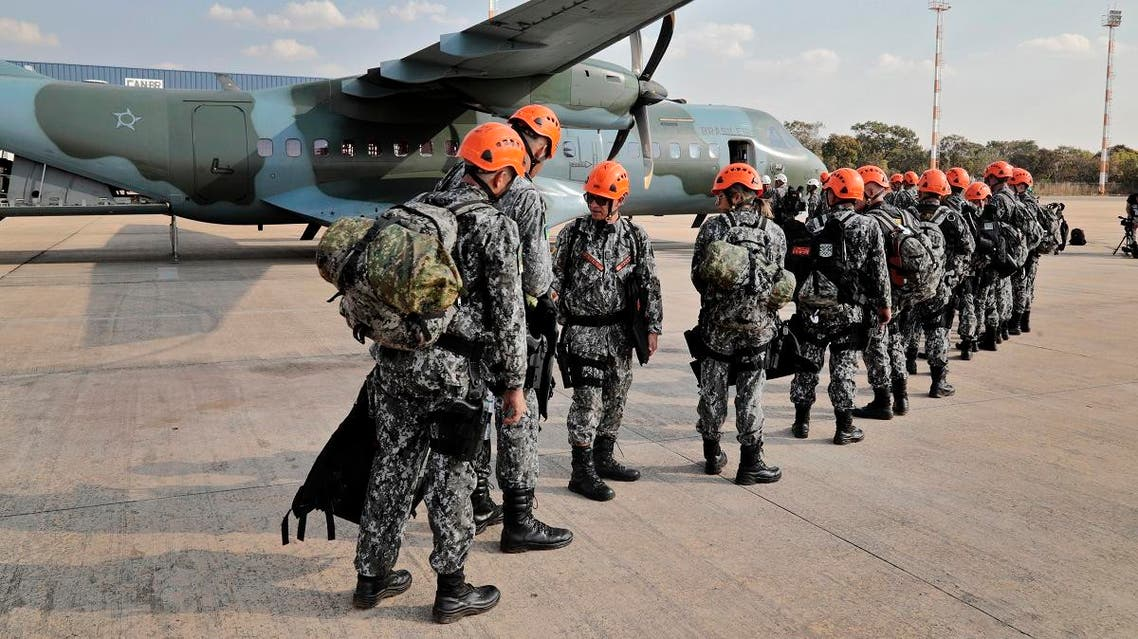 National Force military firefighters stand in line to board a plane to Rondonia northern Brazil, to help fight fires in the Amazon rainforest at the Military Air Base in Brasilia, on August 24, 2019. (AFP)