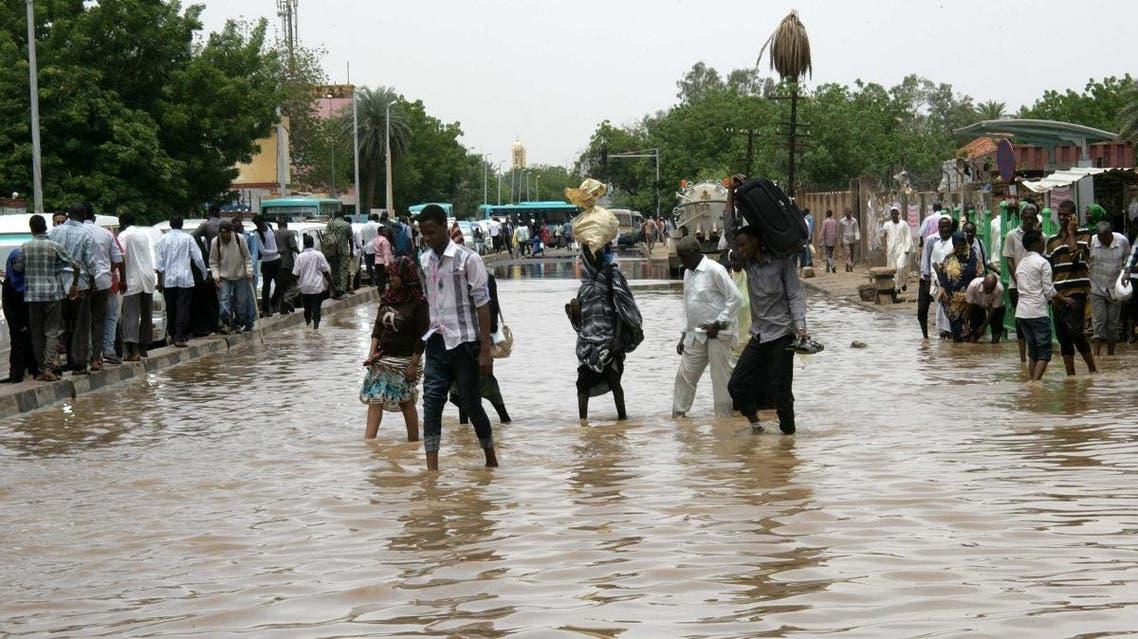 Sudanese cross a flooded street following heavy rain in the capital Khartoum. (File photo: AFP)