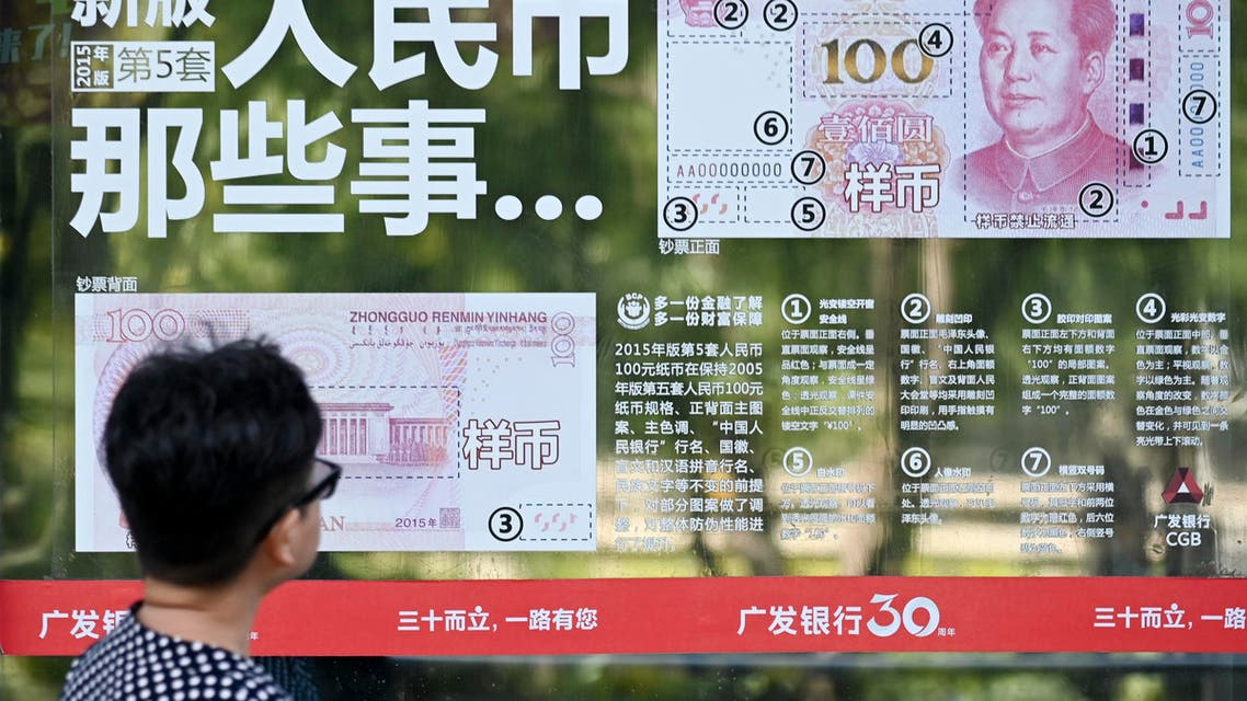 A woman looks at an instructional sticker on a bank door, showing how to distinguish genuine yuan banknotes from counterfeits, in Beijing on August 16, 2019. (AFP)
