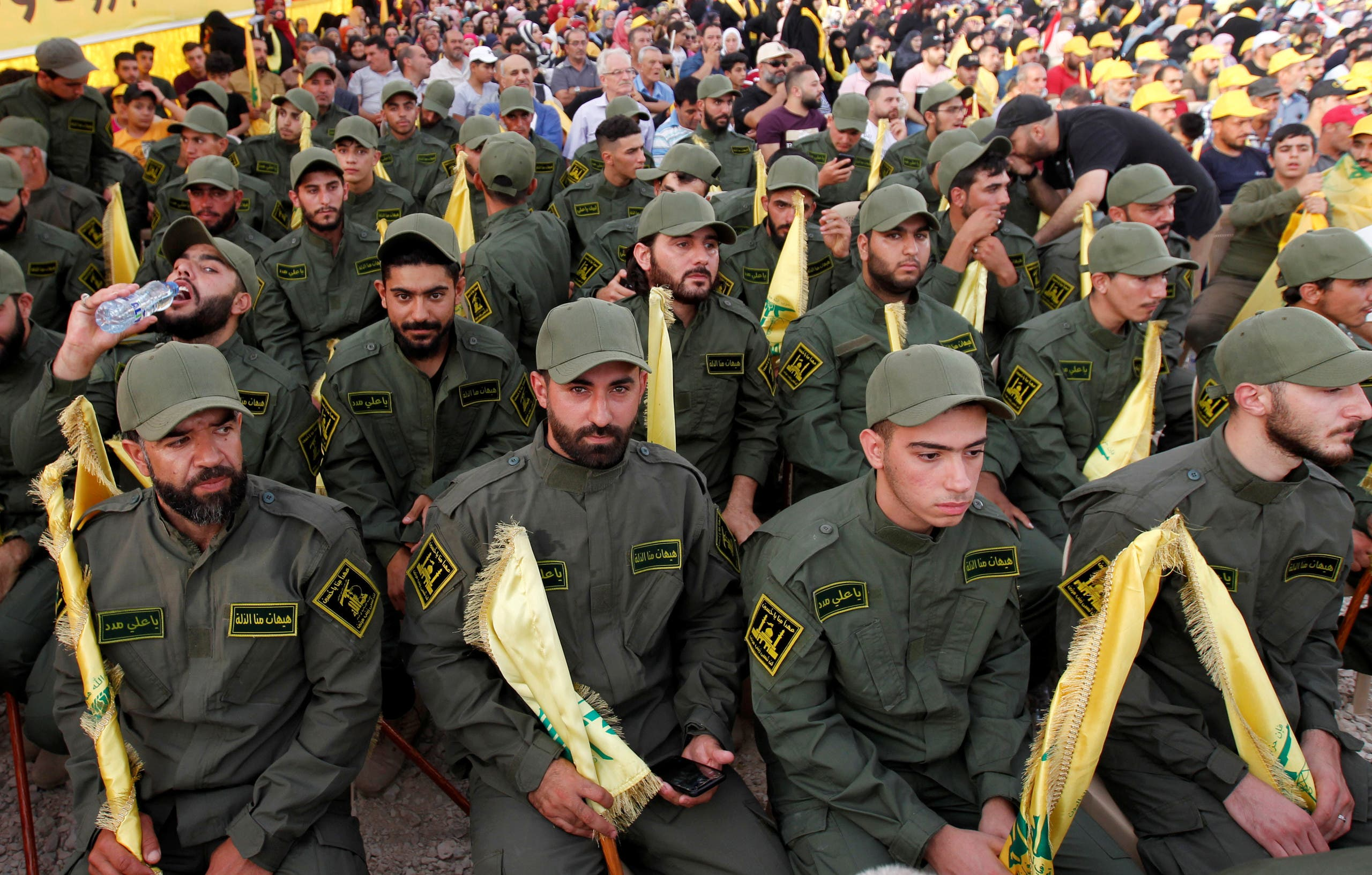 Lebanon's Hezbollah members hold party flags as they listen to their leader Hassan Nasrallah, Aug. 25, 2019. (Reuters)