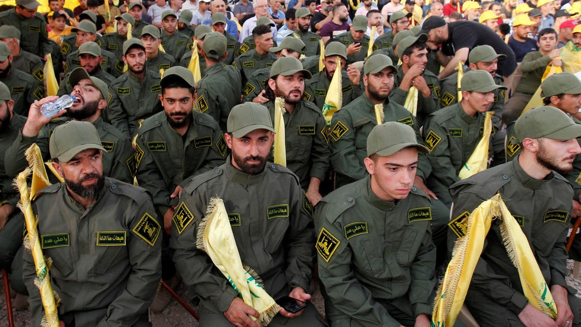 Lebanon's Hezbollah members hold party flags as they listen to their leader Sayyed Hassan Nasrallah addressing his supporters via a screen during a rally marking the anniversary of the defeat of militants near the Lebanese-Syrian border, in al-Ain village, Lebanon August 25, 2019. REUTERS/Aziz Taher