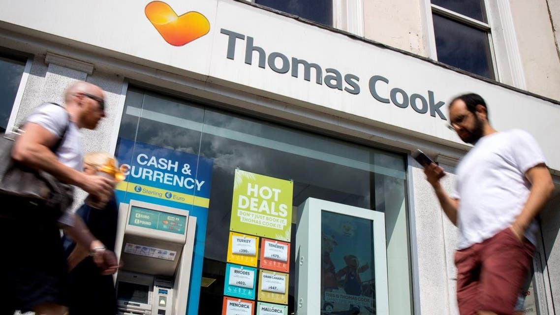 Pedestrians walk past a branch of a Thomas Cook travel agent's shop in London. (File photo: AFP)