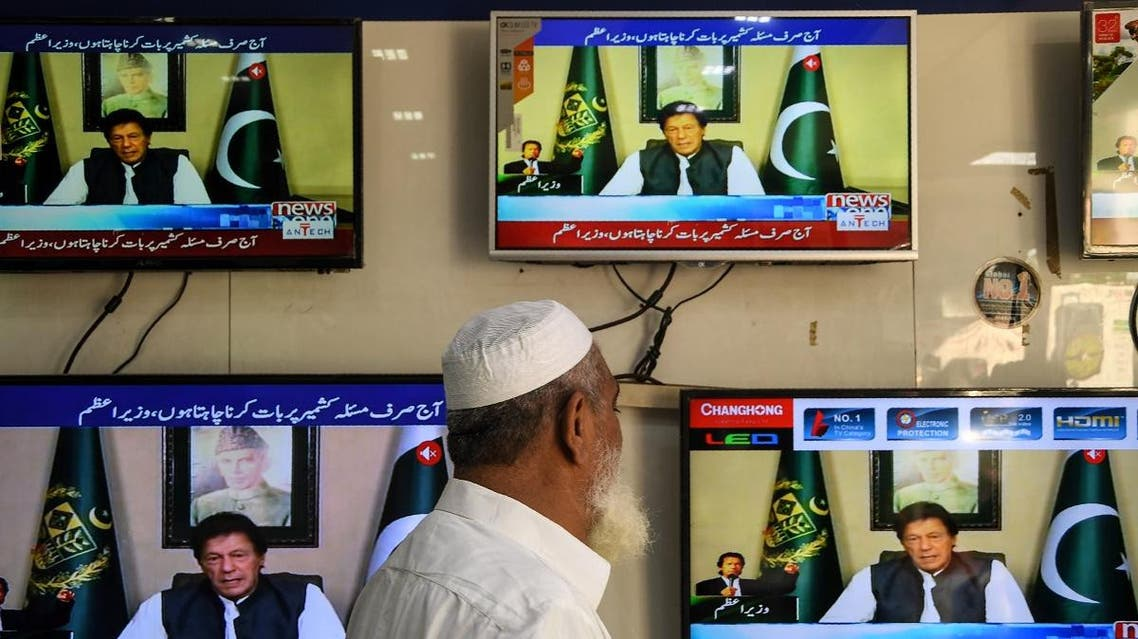 A man watches television as Pakistan's Prime Minister Imran Khan speaks to the nation on disputed Kashmir issues, at an electronic market in Karachi on August 26, 2019. (AFP)