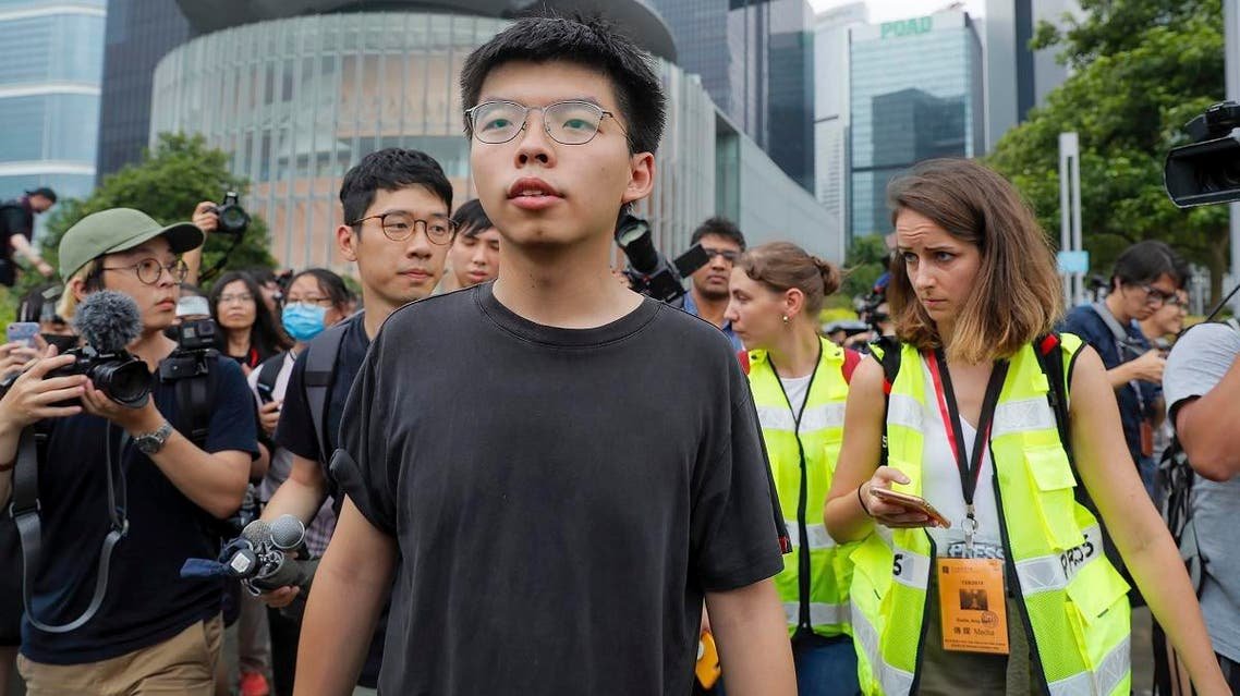 Pro-democracy activist Joshua Wong (center), is chased by reporters after he speaks to protesters near the Legislative Council in Hong Kong. (File photo: AP)