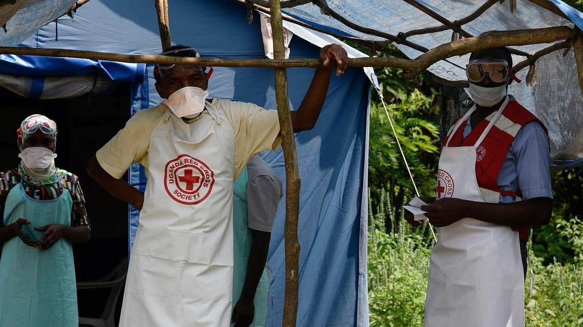 Health workers stand at a non-gazetted crossing point in the Mirami village, near the Mpondwe border check point between Uganda and the Democratic Republic of Congo on June 14, 2019. (AFP)