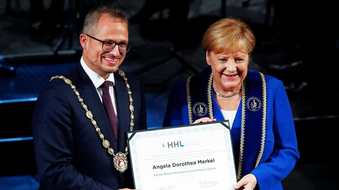 German Chancellor Angela Merkel and Stephan Stubner, Dean of HHL Leipzig Graduate School of Management, pose as she receives an honorary doctorate. (Reuters)