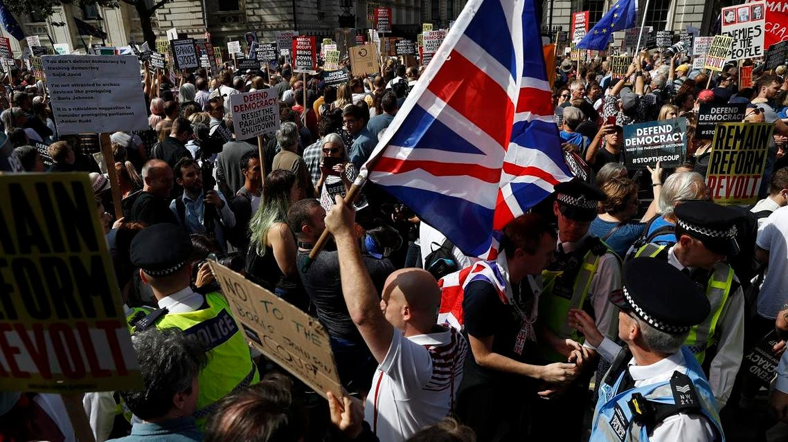 Brexit supporters surrounded by policemen hold British flags as anti Brexit protesters demonstrate during a rally outside Downing Street in London, Saturday, Aug. 31, 2019. (AP)