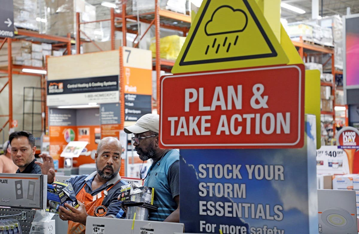 Home Depot worker helps a customer get supplies ahead of the arrival of Hurricane Dorian in Kissimmee. (Reuters)
