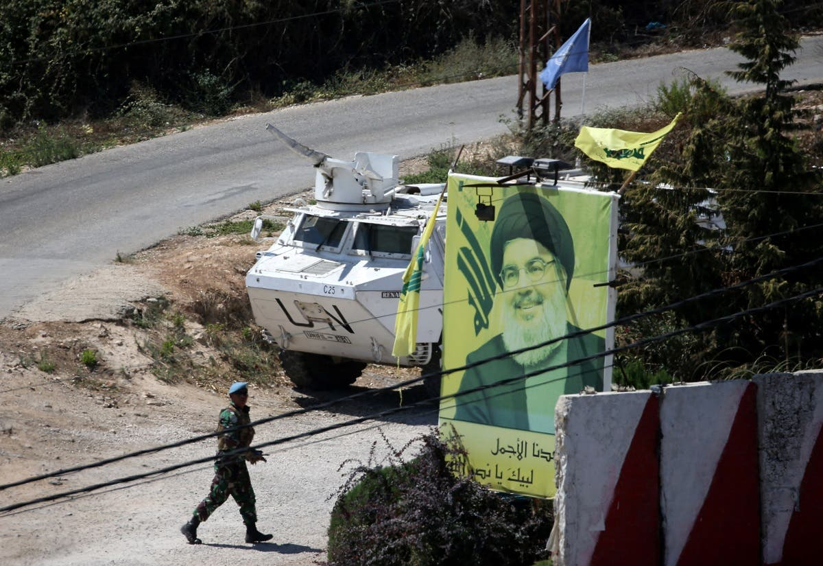 A UN peacekeeper of the United Nations Interim Force in Lebanon (UNIFIL) walks near a poster depicting Lebanon's Hezbollah leader Hassan Nasrallah in Adaisseh. (AFP)