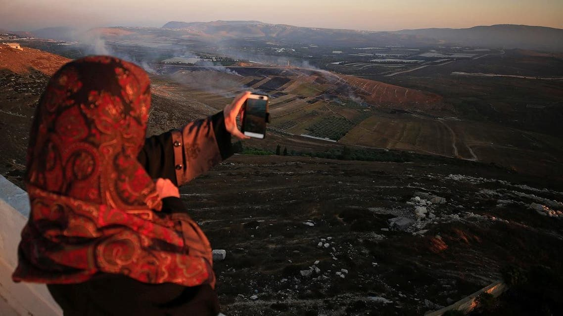 A woman uses her phone as smoke rises from shells fired from Israel in Maroun Al-Ras village, near the border with Israel, in southern Lebanon. (Reuters)
