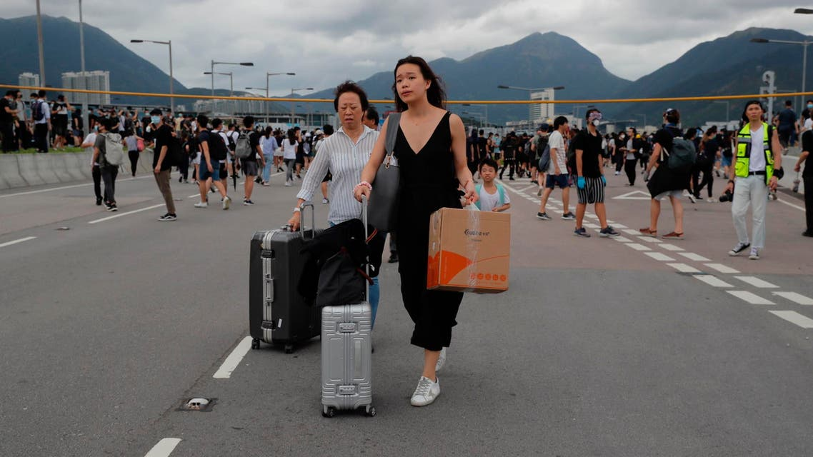 Passengers walk to airport as pro-democracy protestors blocked a road outside the airport in Hong Kong, Sunday, Sept.1, 2019. (AP)