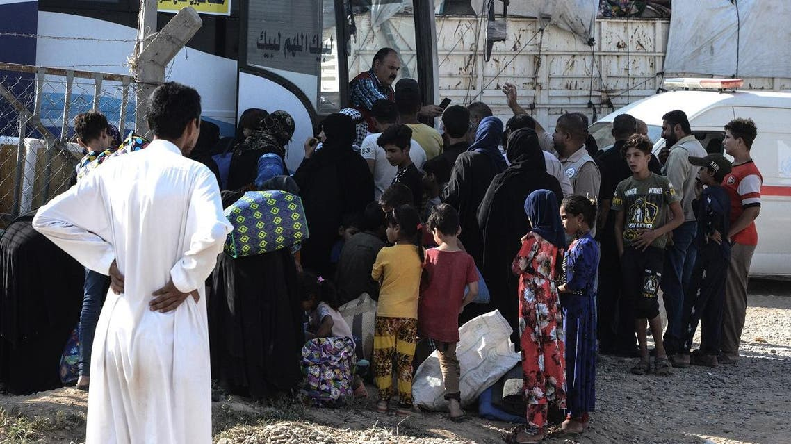 Displaced Iraqis prepare to board a bus at a camp for displaced people in Hammam al-Alil, south of the northern Iraqi city of Mosul, on August 27, 2019, as they are transferred back to Kirkuk province. (AFP)