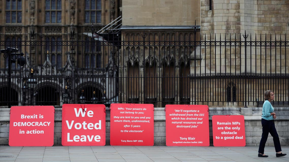 A woman walks past pro-Brexit placards outside the Houses of the Parliament in London, Britain, September 3, 2019. REUTERS