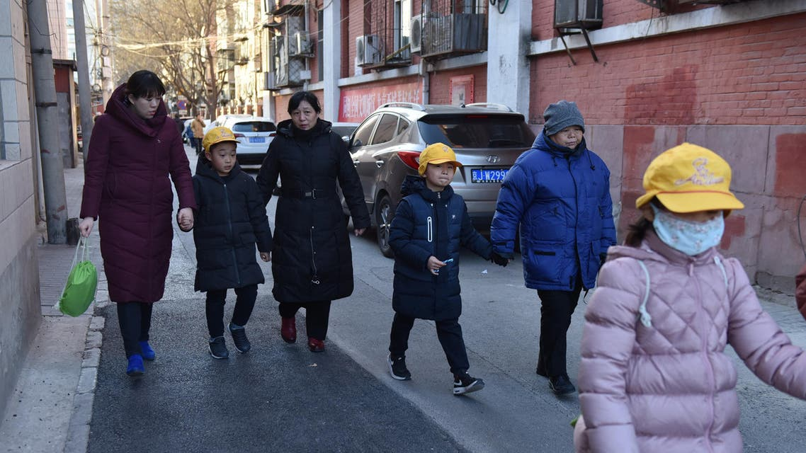 Parents and family members escort their children from an elementary school where an attack took place in Beijing on January 8, 2019. (AFP)