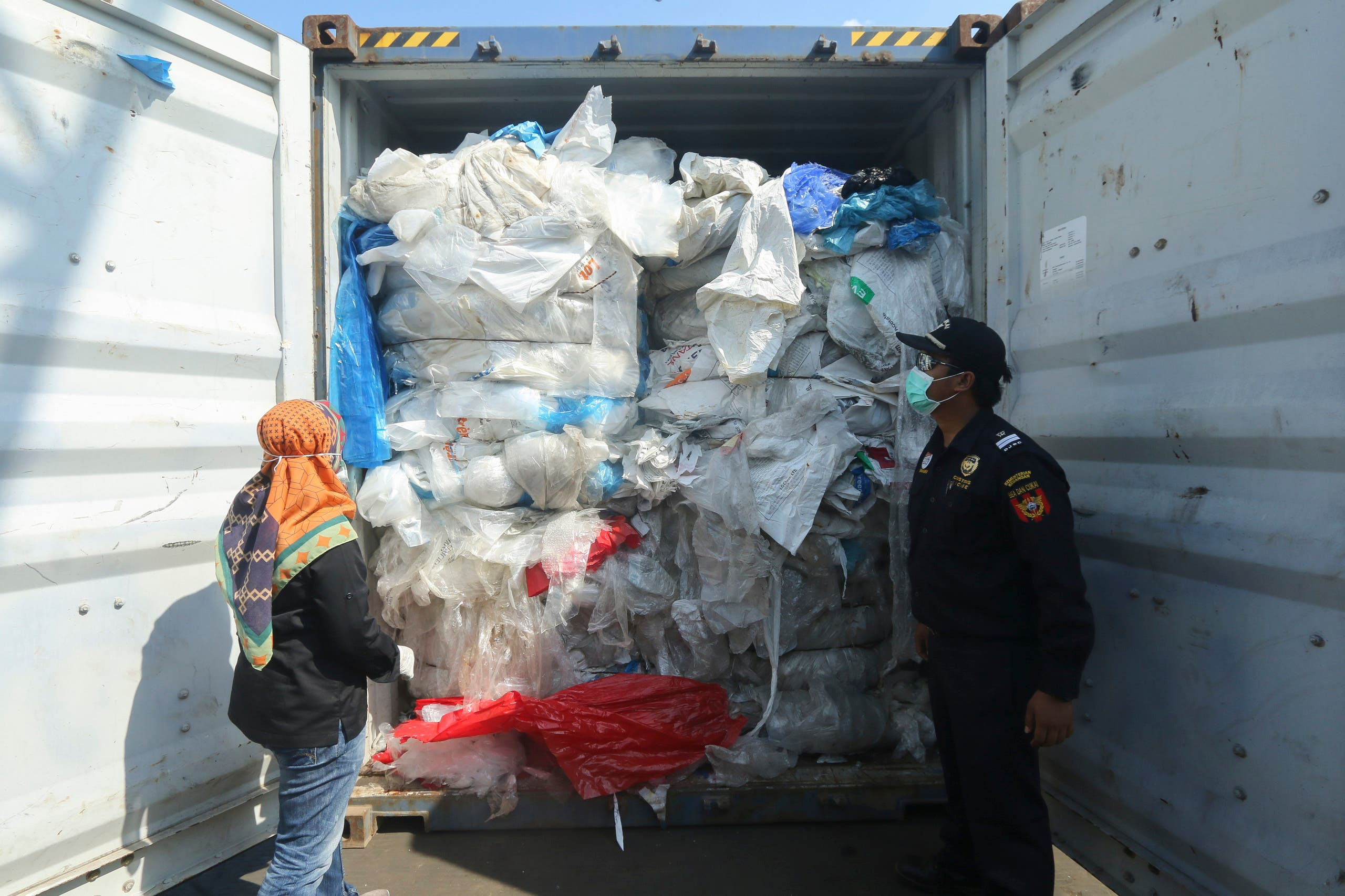 This file photo dated July 29, 2019 shows Indonesian officers checking a container full with illegally imported plastic waste in Batam. (AFP)