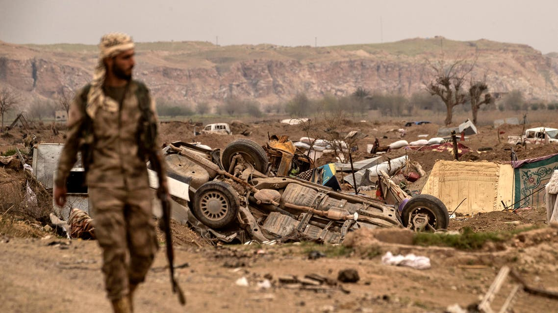A member of the Syrian Democratic Forces (SDF) walks past damaged vehicles on the side of a road in the village of Baghouz in Syria's eastern Deir Ezzor province near the Iraqi border on March 24, 2019, a day after the Islamic State (IS) group's caliphate was declared defeated by the US-backed Kurdish-led Syrian Democratic Forces (SDF).