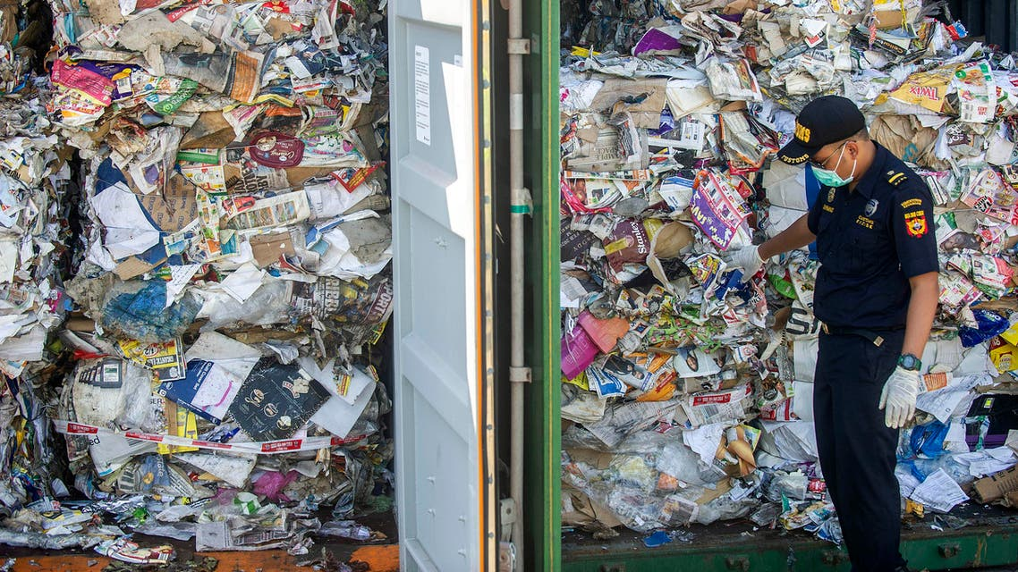 An Indonesian customs officer inspects containers filled with trash originating from Australia, which should have contained only waste paper, but authorities also found hazardous material and household trash, at a port in Surabaya on July 9, 2019. (AFP)