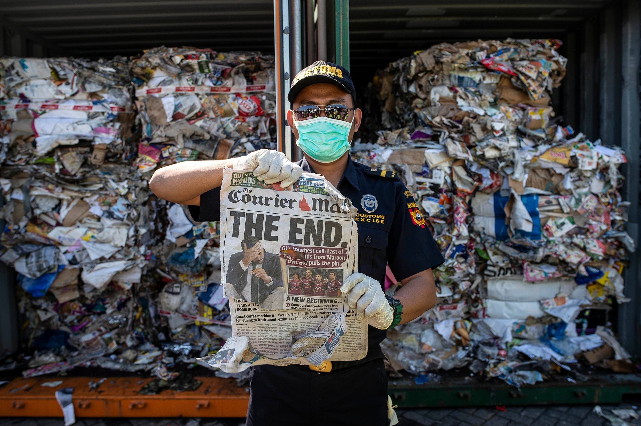 An Indonesian customs officer holds up a newspaper from a container filled with trash originating from Australia, which should have contained only waste paper, but authorities also found hazardous material and household trash, at a port in Surabaya on July 9, 2019. (AFP)