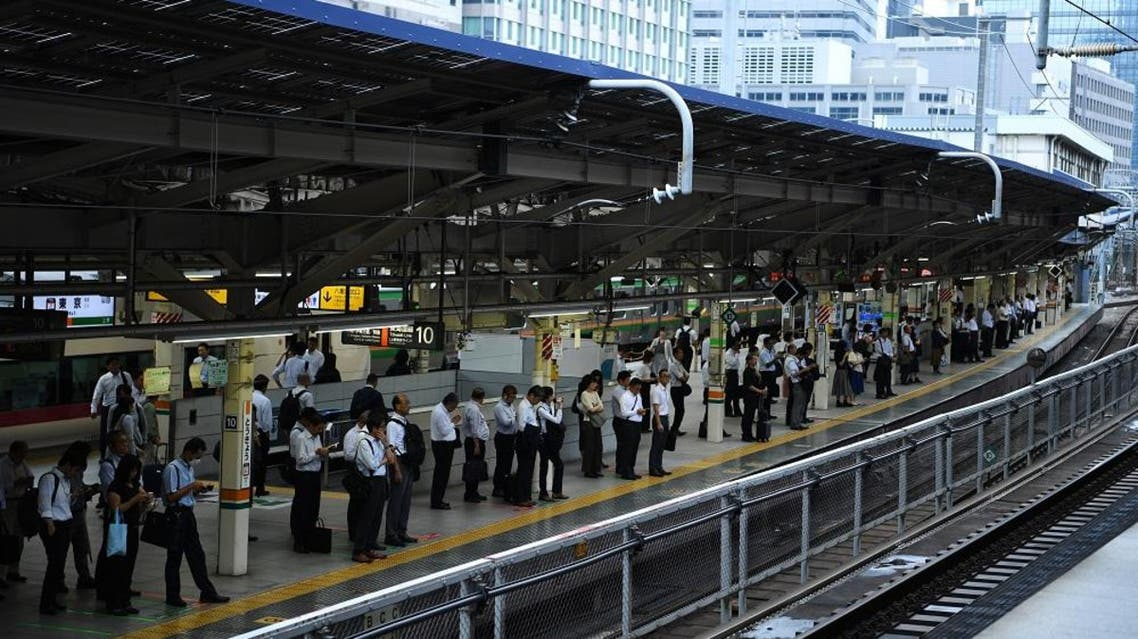 People queue up on the platform ahead of the arrival of a train at Tokyo station on September 5, 2019. (AFP)