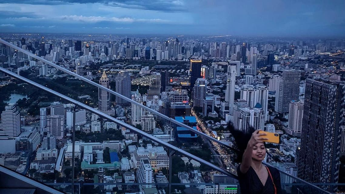 This picture taken on June 26, 2019 shows a tourist taking a selfie photograph in front of the city skyline from the Mahanakorn Skywalk's observation deck area, located 314 metres above the ground, in Bangkok. (AFP)