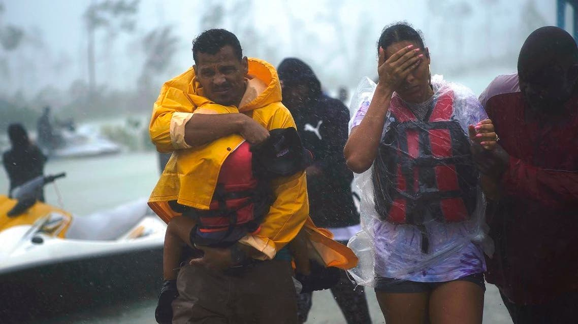 A family is escorted to a safe zone after they were rescued as Hurricane Dorian continues to rain in Freeport, Bahamas. (AP)