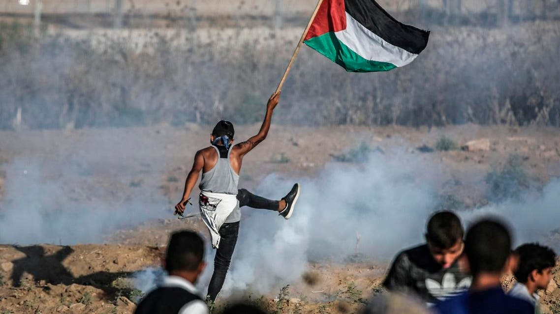 A protester raises a Palestinian flag during clashes with Israeli forces across the border following a demonstration east of Bureij in the central Gaza Strip on September 6, 2019. (AFP)