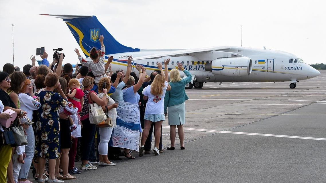 "Friends and relatives waves as a plane carrying former prisoners lands on September 7, 2019 at Boryspil international airport in Kiev after a long-awaited exchange of prisoners between Moscow and Kiev, a day after Russian President said for the first time the ""large-scale"" prisoner exchange with Ukraine was being finalised. (AFP)"