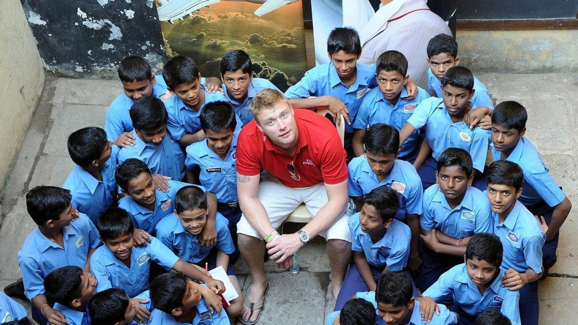 Indian students gather around former England cricketer Andrew Flintoff (C) for a photograph during his visit to the Yusuf Meherali school to donate kits for the school cricket team in Mumbai on November 29, 2010. (AFP)