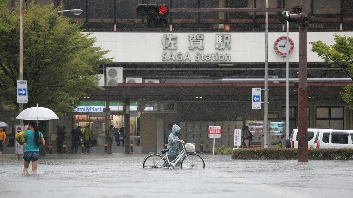 Pedestrians walk in floodwaters after heavy rains outside Saga station in the southwestern city of Saga on August 28, 2019.  (AFP)