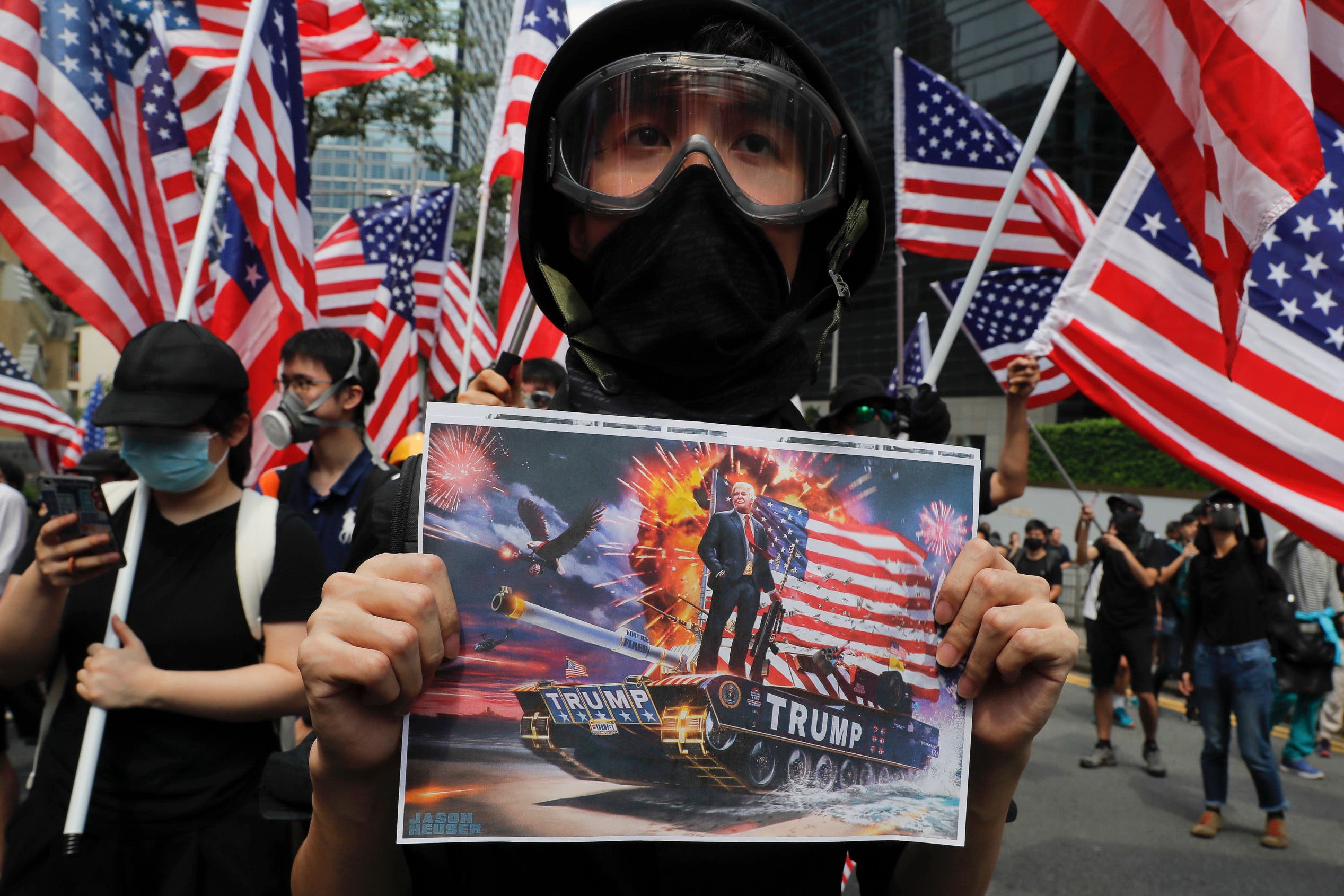 A protester shows a poster of U.S. President Donald Trump as they march with United States flags during a protest in Hong Kong, Sunday, Sept. 8, 2019. (AP)