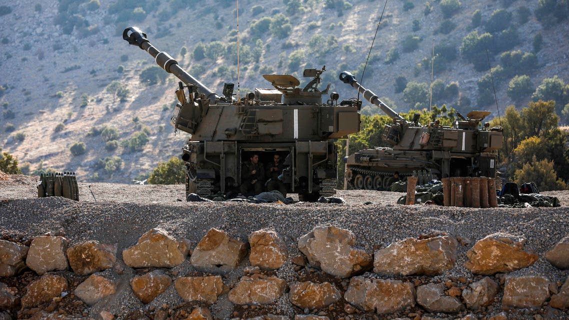 Israeli soldiers sit in the back of a self-propelled artillery gun positioned along the border with Syria in the the Israeli-annexed Golan Heights on August 25, 2019.