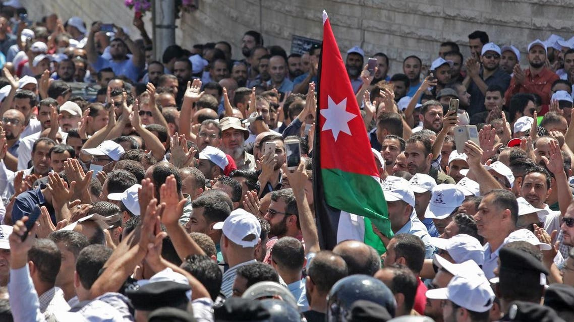 Jordanian teachers chant slogans and wave their national flag during a protest in the capital Amman. (AFP)