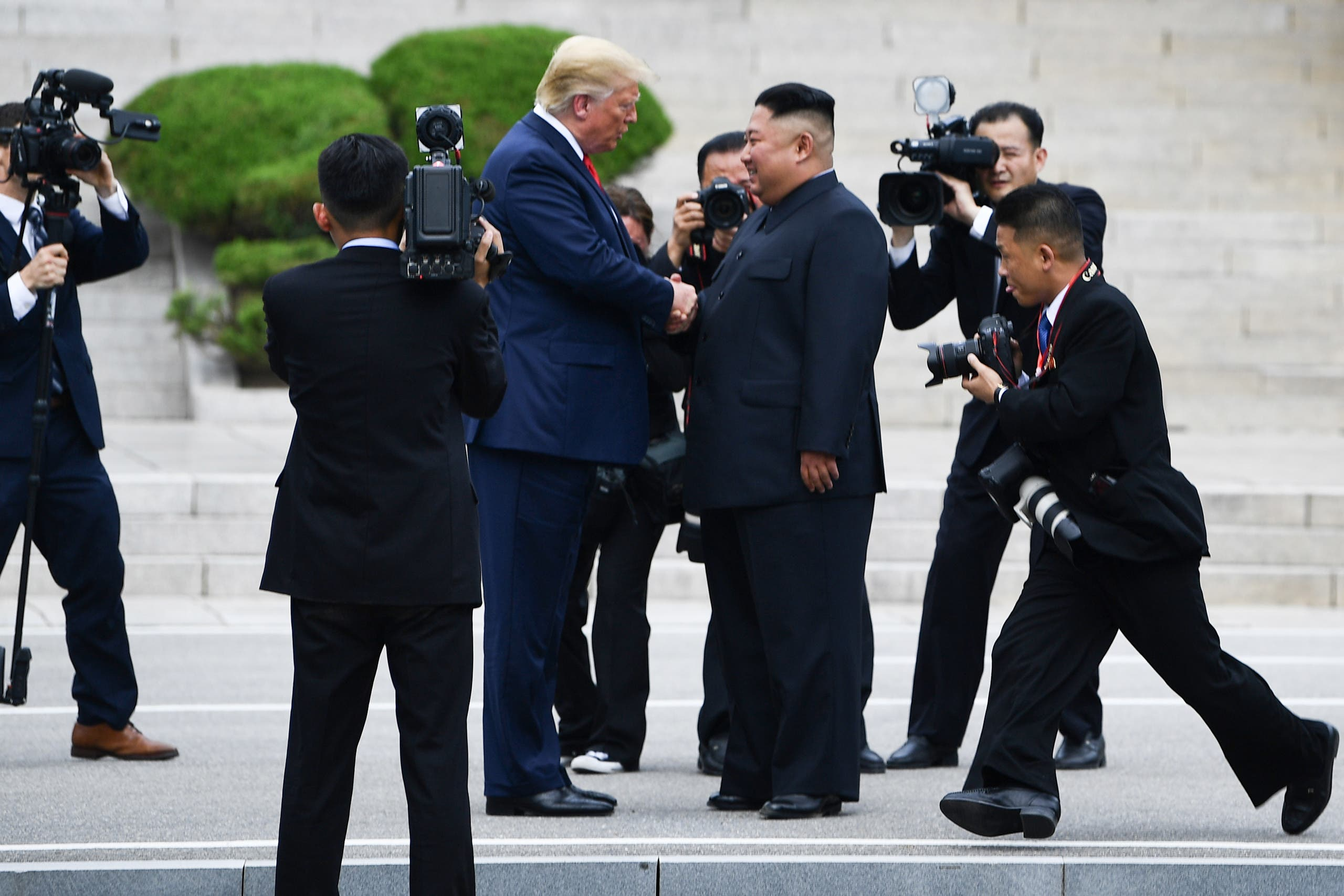 Kim shakes hands with Trump north of the Military Demarcation Line that divides North and South Korea, on June 30, 2019. (AFP)