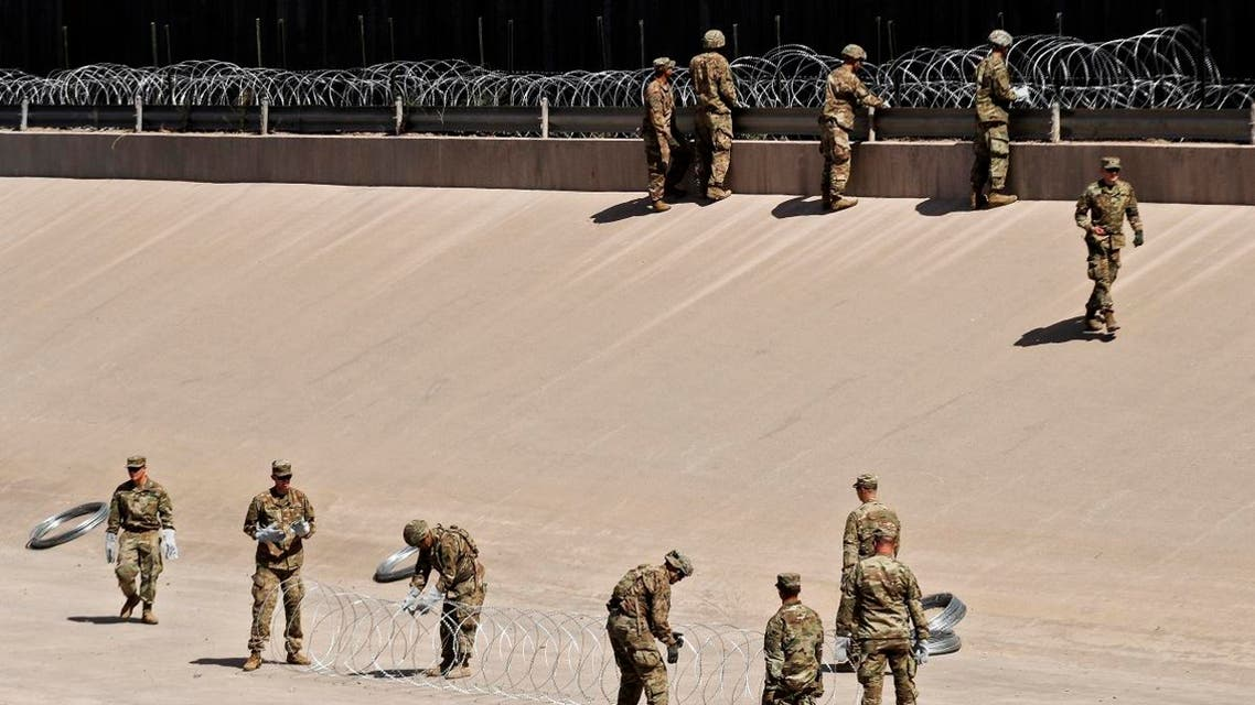 US soldiers install barb wire by the US-Mexico border fence in El Paso, Texas state, US, as seen from Ciudad Juarez, Chihuahua state, Mexico
