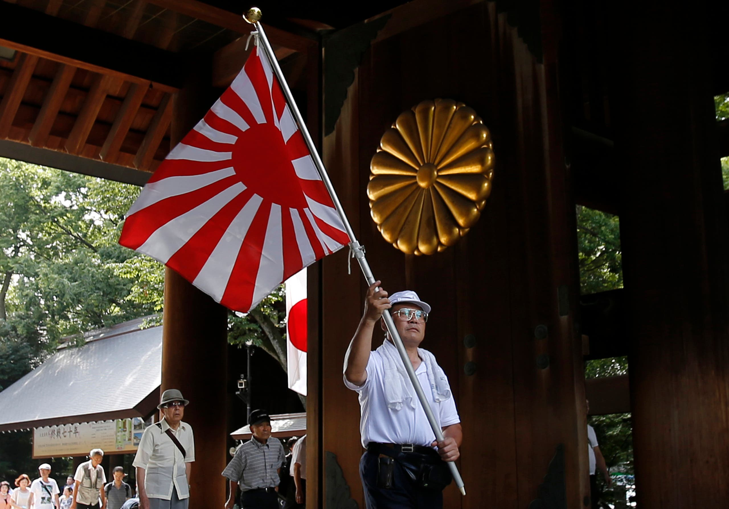A visitor carries a rising sun flag as they come to the Yasukuni Shrine to pay respects to the country's war dead, in Tokyo, Saturday, Aug. 15, 2015. Japan marked Saturday the 70th anniversary of the end of World War II. (File photo: AP)