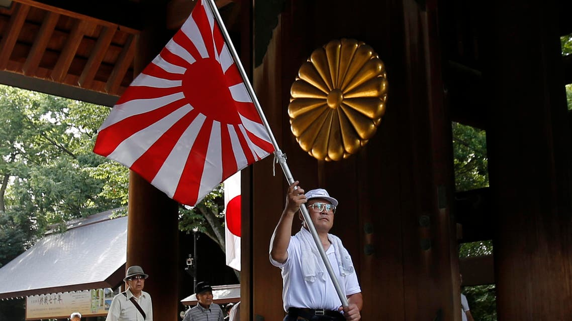 A visitor carries a rising sun flag as they come to the Yasukuni Shrine to pay respects to the country's war dead, in Tokyo, Saturday, Aug. 15, 2015. Japan marked Saturday the 70th anniversary of the end of World War II. (AP Photo/Shuji Kajiyama)
