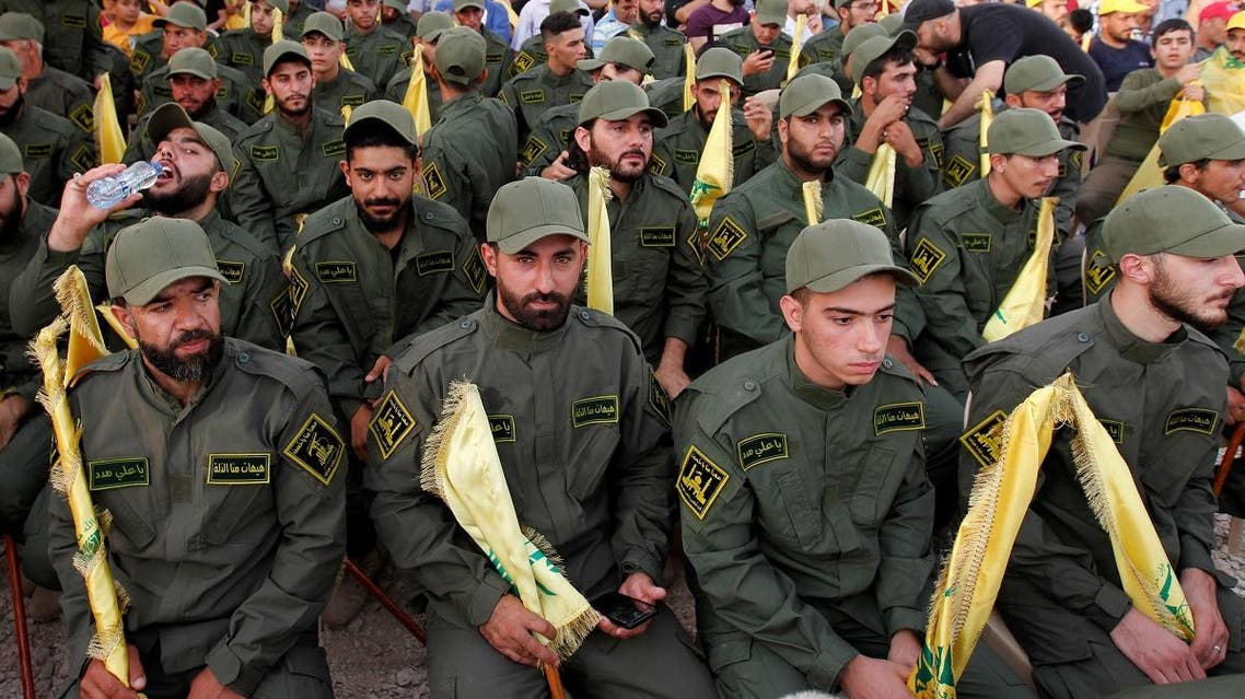 Hezbollah members hold party flags as they listen to their leader Hassan Nasrallah addressing his supporters. (File photo: Reuters)