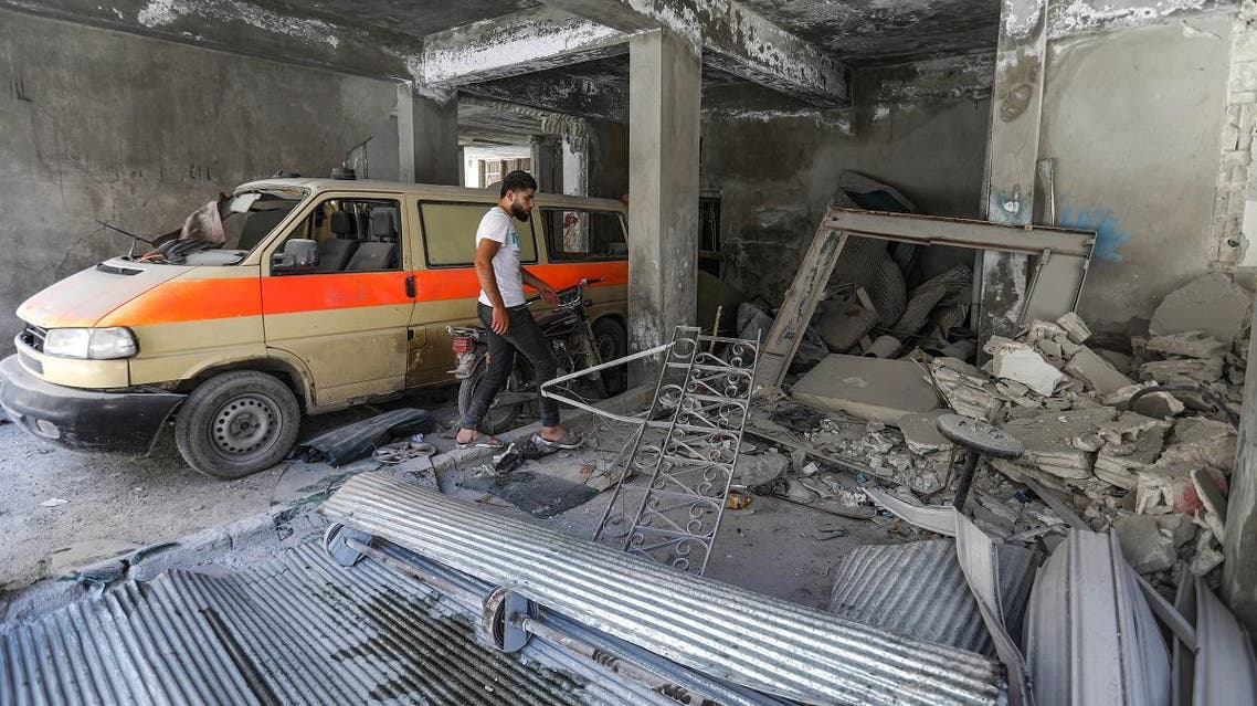 A man walks past a damaged mini-van that was used as a make-shift ambulance amidst debris in the garage of a hospital damaged after a reported air strike in Jisr al-Shughur in the northeastern Syrian Idlib province on July 10, 2019. (AFP)
