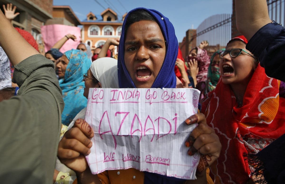 A Kashmiri girl holds a placard as she shouts slogans at a protest site after Friday prayers during restrictions. (Reuters)